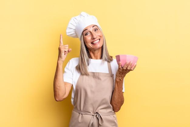 Kobieta szefa kuchni w średnim wieku czując się jak szczęśliwy i podekscytowany geniusz po zrealizowaniu pomysłu, radośnie podnosząc palec, eureka!