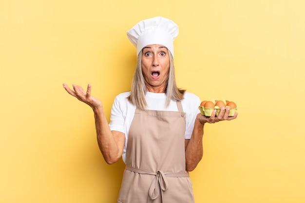 Kobieta szefa kuchni w średnim wieku czuje się bardzo zszokowana i zaskoczona, niespokojna i spanikowana, ze zestresowanym i przerażonym spojrzeniem trzymającym pudełko z jajkami