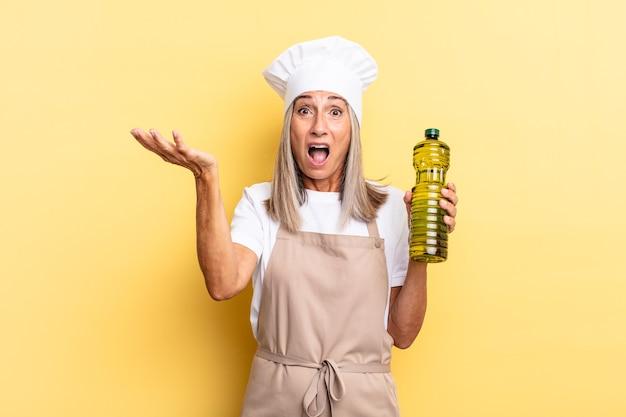 Kobieta szefa kuchni w średnim wieku czuje się bardzo zszokowana i zaskoczona, niespokojna i spanikowana, zestresowana i przerażona