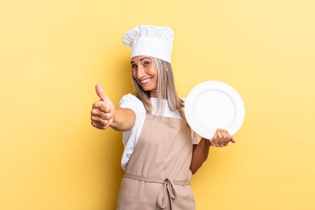 Kobieta szefa kuchni w średnim wieku czuje się dumna, beztroska, pewna siebie i szczęśliwa, uśmiechając się pozytywnie z kciukami w górę i trzymając naczynie