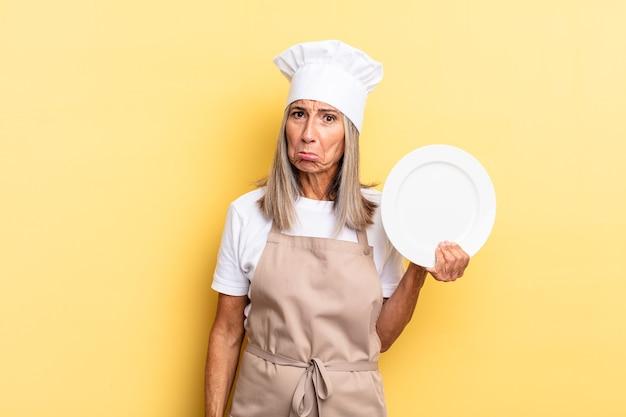 Kobieta szefa kuchni w średnim wieku czuje się smutna i jęczy z nieszczęśliwym spojrzeniem, płacze z negatywnym i sfrustrowanym nastawieniem i trzyma danie