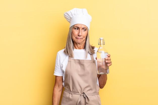 Kobieta szefa kuchni w średnim wieku czuje się smutna, zdenerwowana lub zła i patrzy w bok z negatywnym nastawieniem, marszcząc brwi w niezgodzie z butelką wody