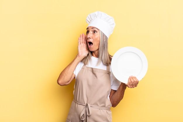 Kobieta szefa kuchni w średnim wieku czuje się szczęśliwa, podekscytowana i zaskoczona, patrząc w bok z obiema rękami na twarzy i trzymając naczynie