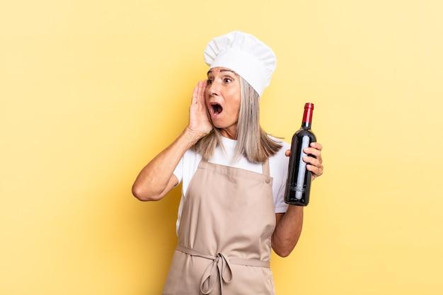 Kobieta szefa kuchni w średnim wieku czuje się szczęśliwa, podekscytowana i zaskoczona, patrząc w bok z obiema rękami na twarzy trzymając butelkę wina
