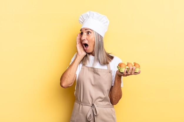 Kobieta szefa kuchni w średnim wieku czuje się szczęśliwa, podekscytowana i zaskoczona, patrząc w bok z obiema rękami na twarzy, trzymająca pudełko z jajkami