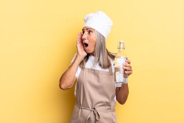 Kobieta szefa kuchni w średnim wieku czuje się szczęśliwa, podekscytowana i zaskoczona, patrząc w bok z obiema rękami na twarzy z butelką wody