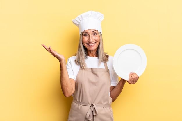 Kobieta szefa kuchni w średnim wieku czuje się szczęśliwa, zaskoczona i pogodna, uśmiechnięta z pozytywnym nastawieniem, realizująca rozwiązanie lub pomysł i trzymająca danie