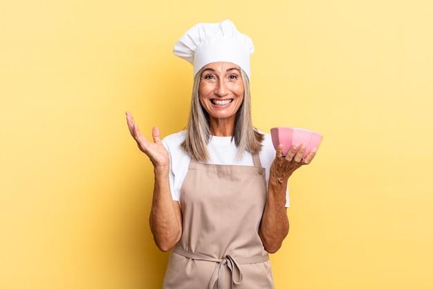 Kobieta szefa kuchni w średnim wieku czuje się szczęśliwa, zaskoczona i wesoła, uśmiechając się z pozytywnym nastawieniem, realizując rozwiązanie lub pomysł i trzymając pusty garnek