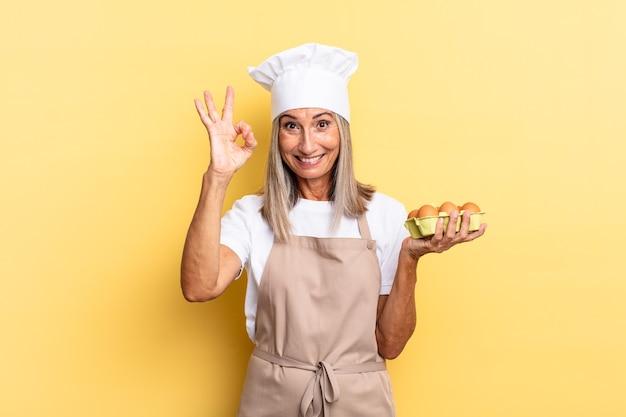 Kobieta szefa kuchni w średnim wieku czuje się szczęśliwa, zrelaksowana i usatysfakcjonowana, okazując aprobatę dobrym gestem, uśmiechając się, trzymając pudełko z jajkami