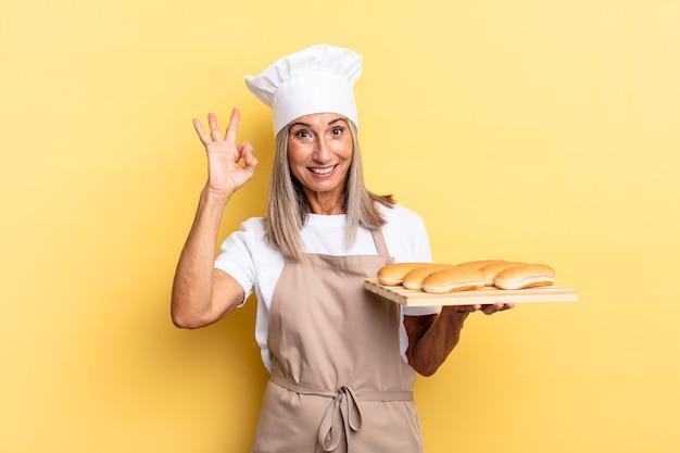 Kobieta szefa kuchni w średnim wieku czuje się szczęśliwa, zrelaksowana i zadowolona, okazując aprobatę dobrym gestem, uśmiechając się i trzymając tacę z chlebem