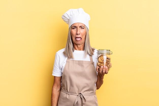 Kobieta szefa kuchni w średnim wieku czuje się zdegustowana i zirytowana, wysuwa język, nie lubi czegoś paskudnego i obrzydliwego z ciasteczkami