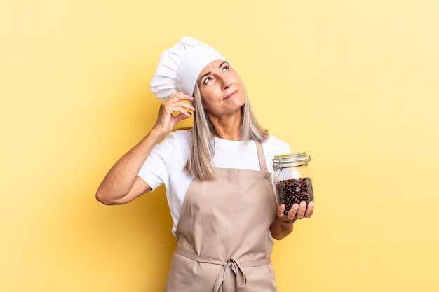 Kobieta szefa kuchni w średnim wieku czuje się zdezorientowana i zdezorientowana, drapiąc się po głowie i patrząc w bok, trzymając ziarna kawy