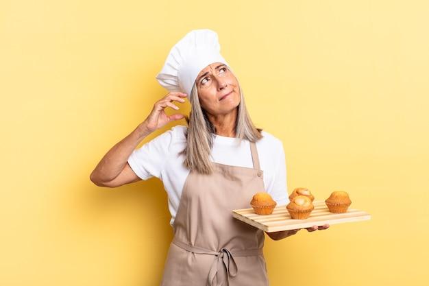Kobieta szefa kuchni w średnim wieku czuje się zdezorientowana i zdezorientowana, drapiąc się po głowie, patrząc w bok i trzymając tacę z babeczkami