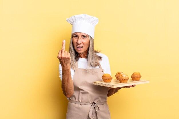 Kobieta szefa kuchni w średnim wieku czuje się zła, zirytowana, buntownicza i agresywna, machając środkowym palcem, walcząc i trzymając tacę z babeczkami
