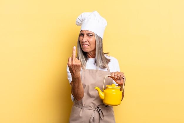 Kobieta szefa kuchni w średnim wieku czuje się zła, zirytowana, buntownicza i agresywna, machając środkowym palcem, walcząc z czajnikiem i trzymając czajniczek