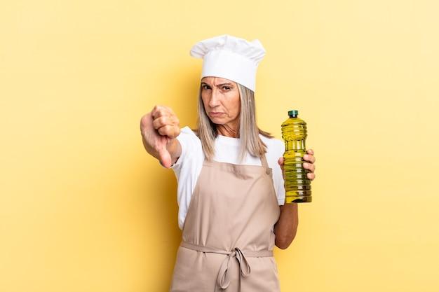 Kobieta szefa kuchni w średnim wieku czuje się zła, zła, zirytowana, rozczarowana lub niezadowolona, pokazując kciuk w dół z poważnym spojrzeniem