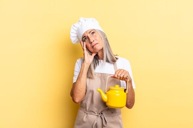 Kobieta szefa kuchni w średnim wieku czuje się znudzona, sfrustrowana i senna po męczącym, nudnym i żmudnym zadaniu, trzymając twarz ręką i trzymając czajnik