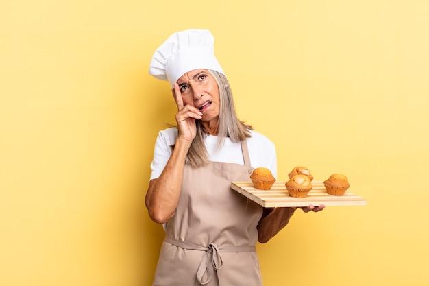 Kobieta szefa kuchni w średnim wieku czuje się znudzona, sfrustrowana i senna po męczącym, nudnym i żmudnym zadaniu, trzymając twarz ręką i trzymając tacę z babeczkami