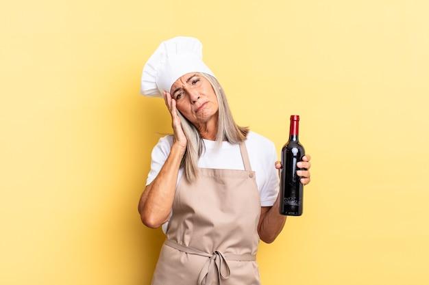 Kobieta szefa kuchni w średnim wieku czuje się znudzona, sfrustrowana i senna po męczącym, nudnym i żmudnym zadaniu, trzymając twarz ręką trzymając butelkę wina