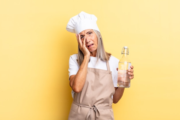Kobieta szefa kuchni w średnim wieku czuje się znudzona, sfrustrowana i senna po męczącym, nudnym i żmudnym zadaniu, trzymając twarz w dłoni z butelką wody