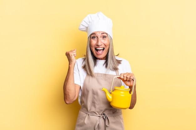 Kobieta szefa kuchni w średnim wieku czuje się zszokowana, podekscytowana i szczęśliwa, śmiejąc się i świętując sukces, mówiąc wow! i trzymając czajniczek