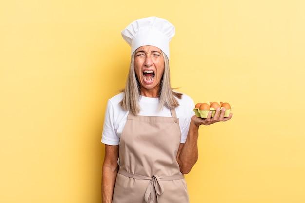 Kobieta szefa kuchni w średnim wieku krzyczy agresywnie, wygląda na bardzo złą, sfrustrowaną, oburzoną lub zirytowaną, krzyczy, że nie trzyma pudełka z jajkami