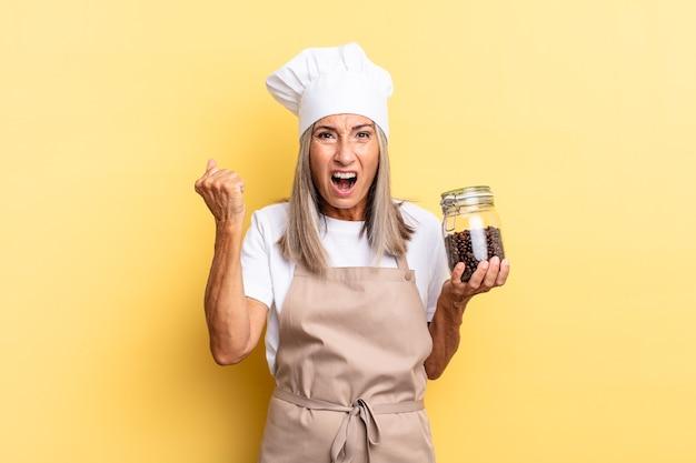 Kobieta szefa kuchni w średnim wieku krzyczy agresywnie z gniewnym wyrazem twarzy lub z zaciśniętymi pięściami, świętując sukces trzymając ziarna kawy