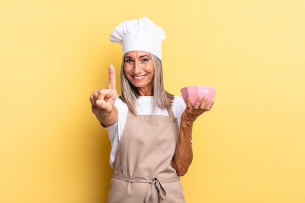 Kobieta szefa kuchni w średnim wieku, uśmiechnięta dumnie i pewnie, triumfalnie wykonując pozę numer jeden, czując się jak liderka i trzymając pusty garnek