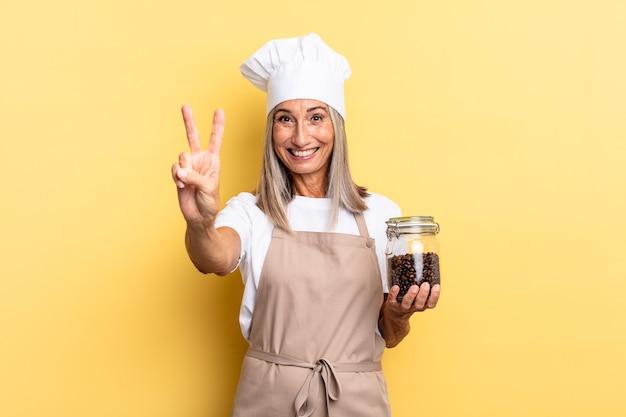 Kobieta szefa kuchni w średnim wieku uśmiechnięta i wyglądająca na szczęśliwą, beztroską i pozytywną, gestykulującą zwycięstwo lub pokój jedną ręką trzymającą ziarna kawy
