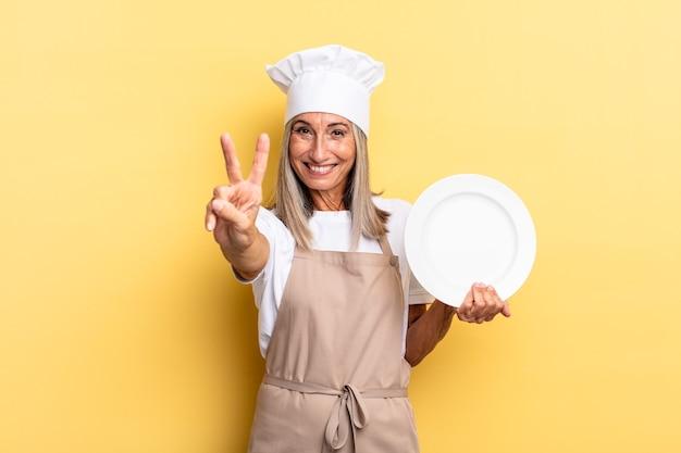 Kobieta szefa kuchni w średnim wieku uśmiechnięta i wyglądająca przyjaźnie, pokazująca numer dwa lub drugi z ręką do przodu, odliczającą i trzymającą naczynie