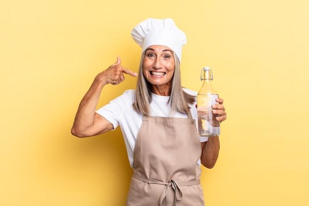Kobieta szefa kuchni w średnim wieku uśmiechnięta pewnie, wskazując na swój szeroki uśmiech, pozytywna, zrelaksowana, zadowolona postawa z butelką wody
