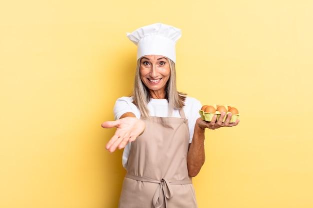 Kobieta szefa kuchni w średnim wieku uśmiechnięta radośnie z przyjaznym, pewnym siebie, pozytywnym spojrzeniem, oferująca i pokazująca przedmiot lub koncepcję trzymającą pudełko z jajkami