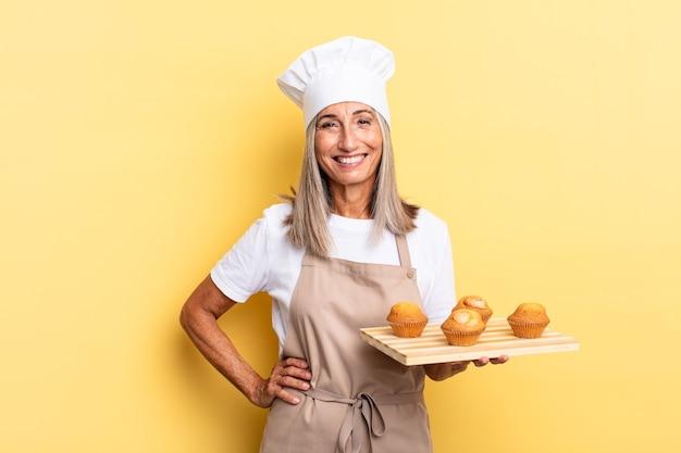 Kobieta szefa kuchni w średnim wieku uśmiechnięta radośnie z ręką na biodrze i pewna siebie, pozytywna, dumna i przyjazna i trzymająca tacę z babeczkami