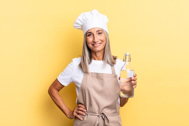 Kobieta szefa kuchni w średnim wieku uśmiechnięta radośnie z ręką na biodrze i pewna siebie, pozytywna, dumna i przyjazna postawa z butelką wody