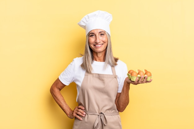 Kobieta szefa kuchni w średnim wieku uśmiechnięta radośnie z ręką na biodrze i pewna siebie, pozytywna, dumna i przyjazna, trzymająca pudełko z jajkami