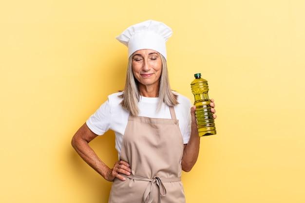 Kobieta szefa kuchni w średnim wieku uśmiechnięta radośnie z ręką na biodrze i pewna siebie, pozytywna, dumna i przyjazna
