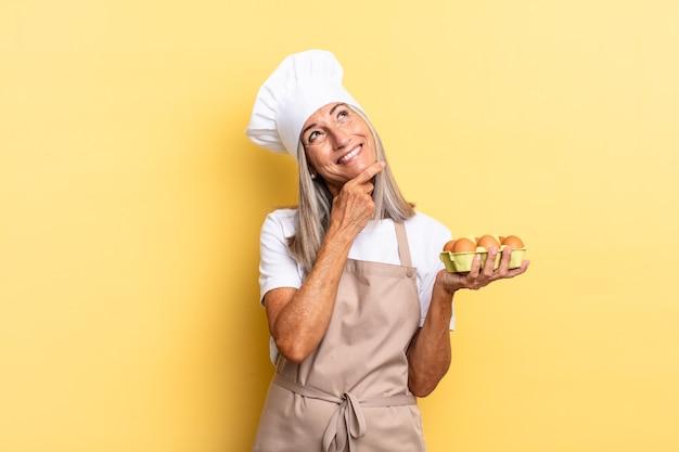 Kobieta szefa kuchni w średnim wieku uśmiechnięta ze szczęśliwym, pewnym siebie wyrazem twarzy z ręką na brodzie, zastanawiająca się i patrząca w bok, trzymająca pudełko z jajkami