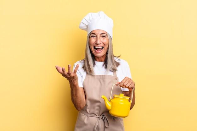 Kobieta szefa kuchni w średnim wieku wygląda na złą, zirytowaną i sfrustrowaną, krzycząc wtf lub co jest z tobą nie tak i trzyma czajniczek