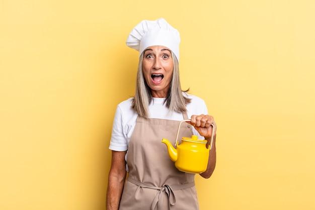 """Kobieta szefa kuchni w średnim wieku, wyglądająca na bardzo zszokowaną lub zaskoczoną, patrząca z otwartymi ustami, mówiąca """"wow"""" i trzymająca czajnik"""