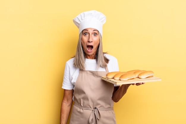 """Kobieta szefa kuchni w średnim wieku, wyglądająca na bardzo zszokowaną lub zaskoczoną, patrząca z otwartymi ustami, mówiąca """"wow"""" i trzymająca tacę z chlebem"""