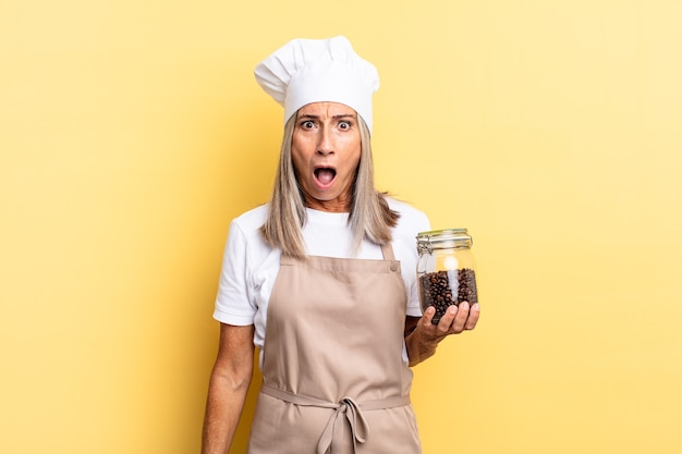 """Kobieta szefa kuchni w średnim wieku, wyglądająca na bardzo zszokowaną lub zaskoczoną, patrząca z otwartymi ustami, mówiąca """"wow"""", trzymając ziarna kawy"""
