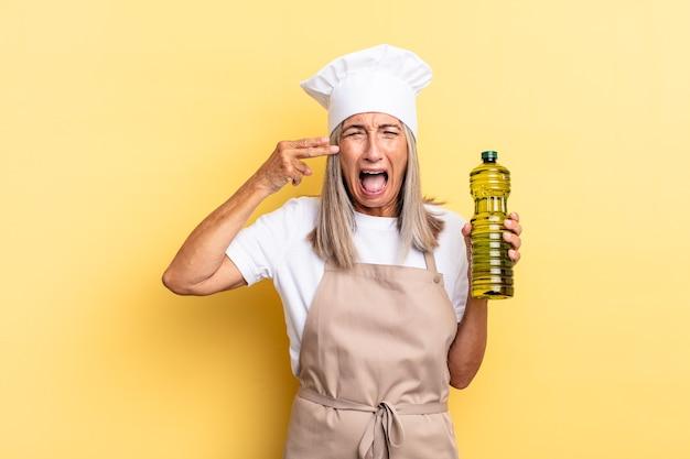 Kobieta szefa kuchni w średnim wieku wyglądająca na niezadowoloną i zestresowaną, gest samobójczy wykonujący znak pistoletu ręką, wskazujący na głowę