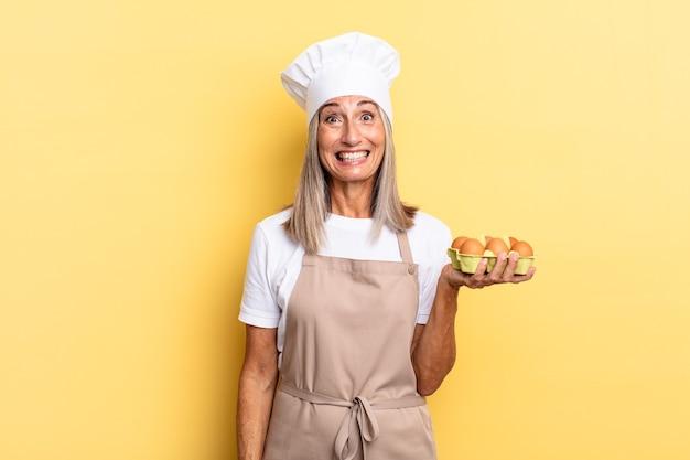 Kobieta szefa kuchni w średnim wieku wyglądająca na szczęśliwą i mile zaskoczoną, podekscytowaną z zafascynowanym i zszokowanym wyrazem twarzy, trzymająca pudełko z jajkami