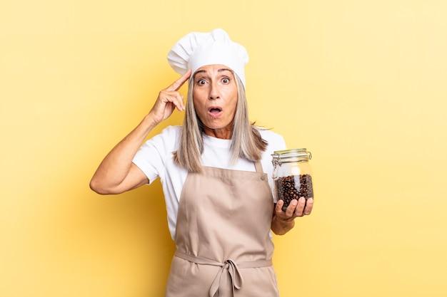 Kobieta szefa kuchni w średnim wieku wyglądająca na szczęśliwą, zdziwioną i zaskoczoną, uśmiechniętą i zdającą sobie sprawę z niesamowitych i niewiarygodnych dobrych wiadomości z ziarnami kawy
