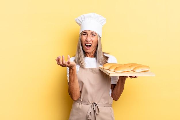 Kobieta szefa kuchni w średnim wieku wyglądająca na zdesperowaną i sfrustrowaną, zestresowaną, nieszczęśliwą i zirytowaną, krzyczącą i krzyczącą i trzymającą tacę z chlebem
