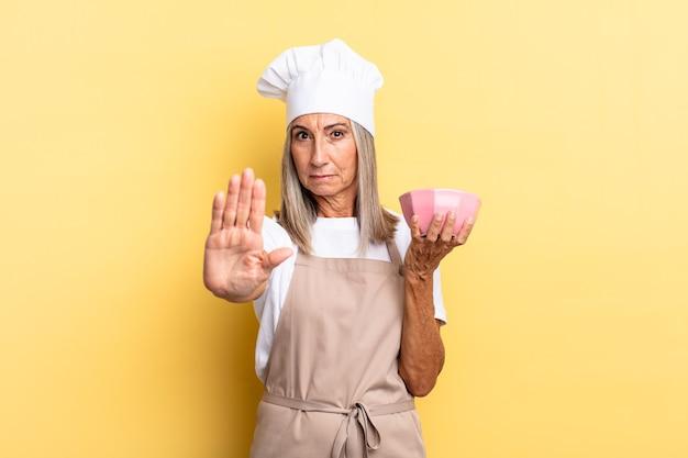 Kobieta szefa kuchni w średnim wieku wyglądająca poważnie, surowo, niezadowolona i zła, pokazując otwartą dłoń, wykonując gest zatrzymania i trzymając pusty garnek