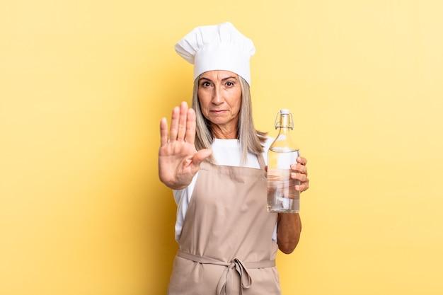 Kobieta szefa kuchni w średnim wieku wyglądająca poważnie, surowo, niezadowolona i zła, pokazując otwartą dłoń wykonującą gest zatrzymania z butelką wody