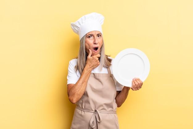 Kobieta szefa kuchni w średnim wieku z szeroko otwartymi ustami i oczami i ręką na brodzie, czując się nieprzyjemnie zszokowana, mówiąc co lub wow i trzymając danie