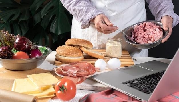 Kobieta szefowa kuchni gotuje dużego burgera lub cheeseburgera i korzysta z laptopa z samouczkiem z przepisami kulinarnymi.