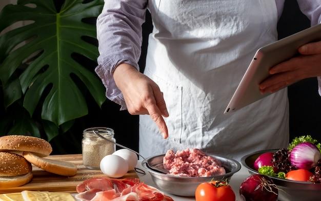 Kobieta szefowa kuchni gotuje dużego burgera lub cheeseburgera i używa tabletu z samouczkiem z przepisami kulinarnymi.